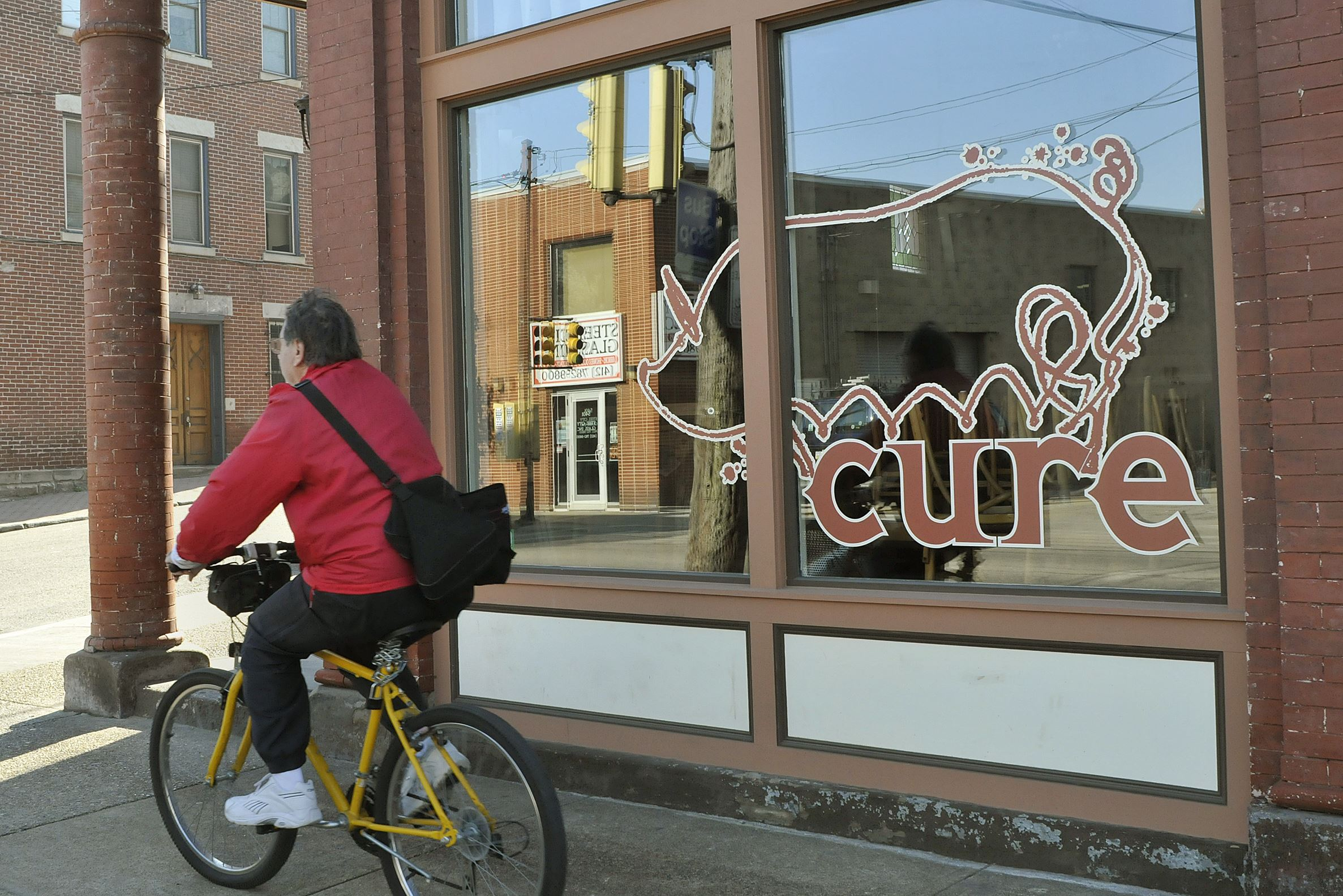 cure A bicyclist rides past Cure on Butler Street in Lawrenceville.