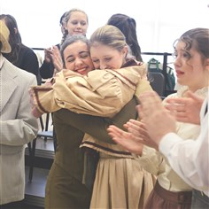 "Music Man Sophomore Erika Levine hugs senior Cara Lyons after their backstage warmups before performing in South Fayette High School's production of ""The Music Man."""