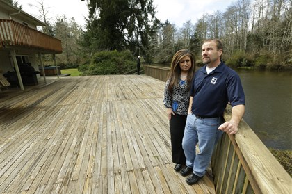 Flood Insurance Darrin Moir, right, and his wife Leonor Moir, stand on the deck of their house along the Little Hoquiam River in Hoquiam, Wash. The Moirs pay about $1,700 annually for flood insurance, even though they say they have never had a major flooding incident since buying their home in 1996. Possible rate increases could increase their premiums to more than $9,000 a year, which they say could prevent them from eventually selling their home.