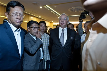 Malaysian Prime Minister Malaysian Prime Minister Najib Razak, center, walks out of a news conference Monday giving an update of the missing Malaysia Airlines flight MH370 at the Putra World Trade Center in Kuala Lumpur.