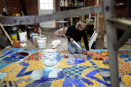 "James Simon Artist James Simon glues down some final pieces of glass on his mosaic, ""The Skateboarders."""