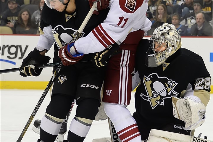 20140325pdPenguinsSports02-1 Penguins goalie Marc-Andre Fleury makes the save but loses sight of the puck while being blocked by the Coyotes' Martin Hanzal.
