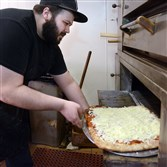 Anthony Badamo slides his Sicilian pizza into the oven at his shop in Mt. Lebanon shop in this 2014 photo. He'll open a second location on the North Side later this year.