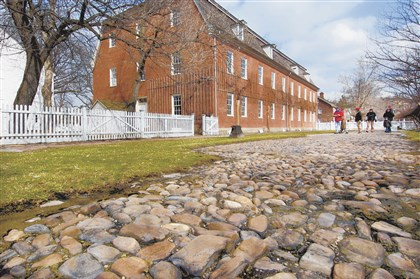 Old Economy Visitors cross the Cobblestone street outside the Feast Hall on their tour Old Economy Village in Ambridge.