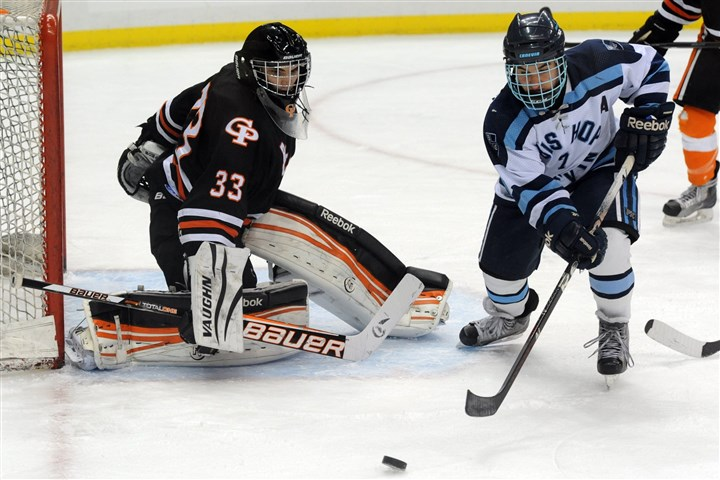 Photographer Bishop Canevin's Garrett Godlewski tries to steer the puck around Erie Cathedral Prep goalie Grant Kennedy during the Penguins Cup Class AA title game at Consol Energy Center.