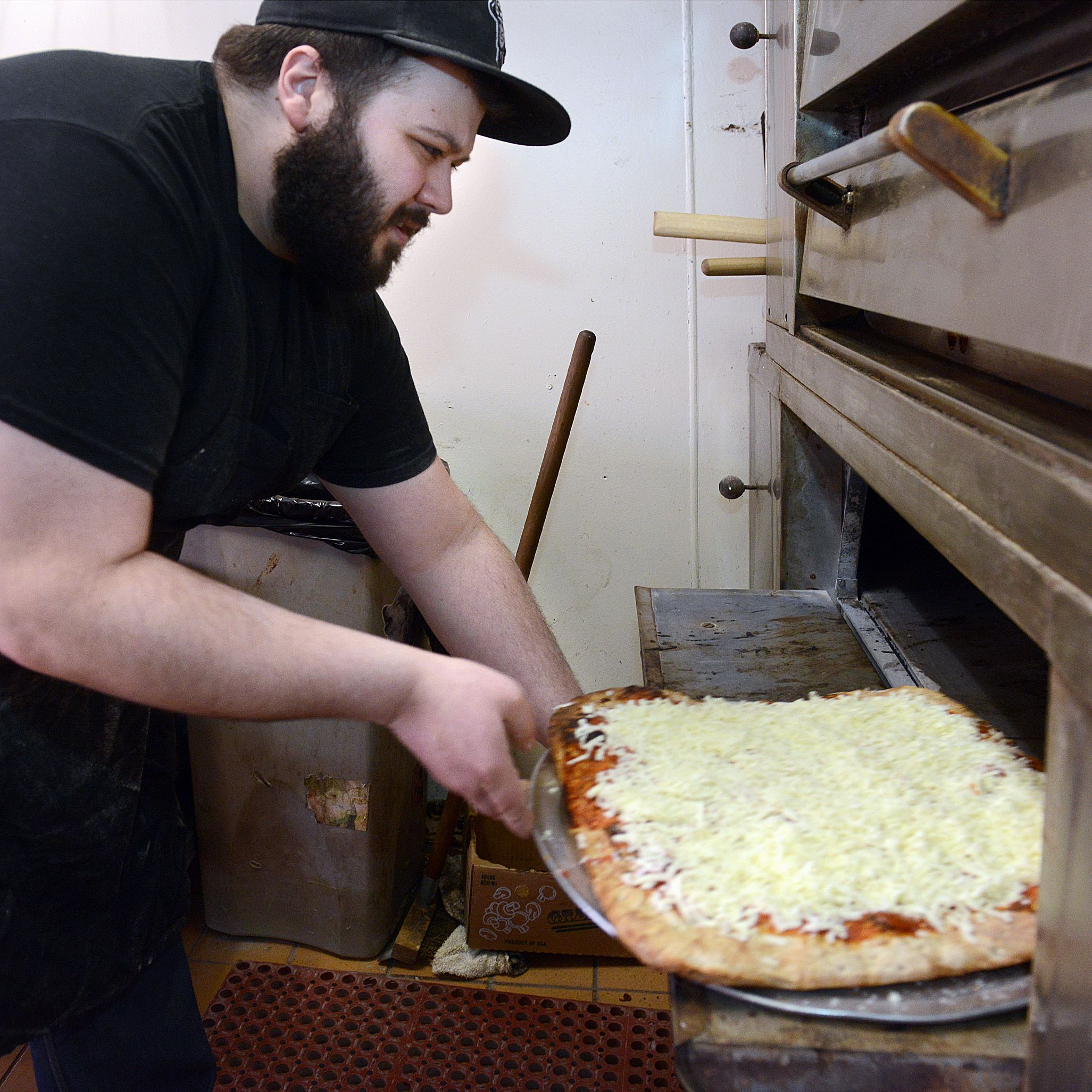 20140326radApizzaBadamoMag02-1 Anthony Badamo slides his Sicilian pizza into the oven at his shop in Mt. Lebanon shop in this 2014 photo. He'll open a second location on the North Side later this year.