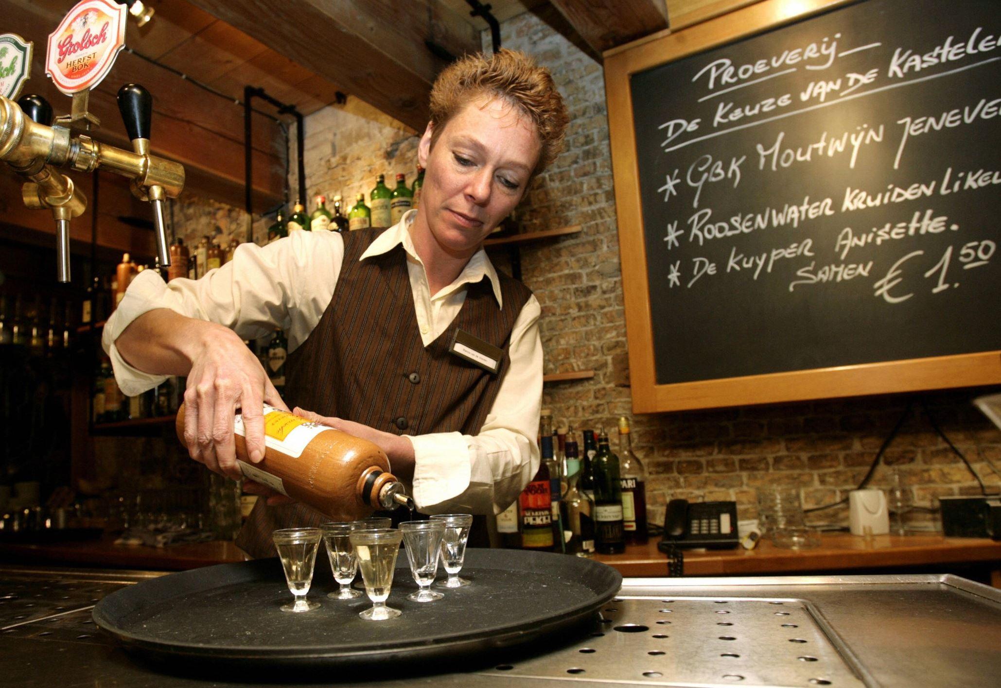 20140329gettygeneverfood01 Hostess Bianca van de Vooren pours jenever into traditional jenever taste glasses in the bar of the Jenever Museum in Schiedam, the Netherlands.
