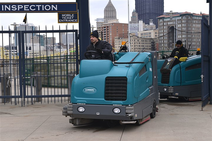 20140330lrpiratesstandalone02-1 Workers at PNC Park bring the riding scrubbers through the gate on Sunday after clearning up the area in time for today's home opener.