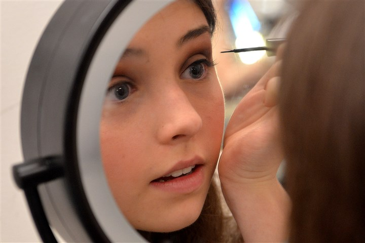 Millie Emily Weinhoffer, 16, a sophomore who plays Gloria, takes care applying her eye makeup.