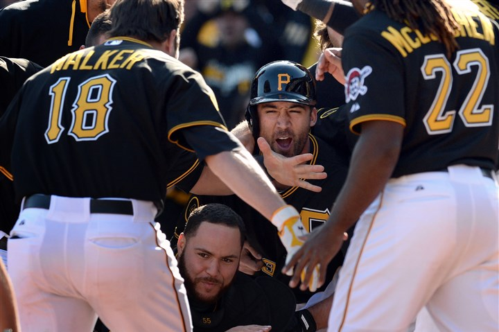 20140331mfbucssports16-1 Pirates teammates congratulate Neil Walker on Monday after he hit a home run in the 10th inning to win the game against the Cubs at PNC Park.