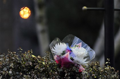 20140401JHSchlemmer A bouquet of flowers sits in the shrubs outside the McCandless home where two children were found unconscious in the bathroom after their mother admittedly sat on them in a bathtub filled with water.