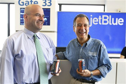 Food Craft Beer Airlines Jim Koch, founder and brewer of Samuel Adams and Marty St. George, SVP of Marketing and Commercial at JetBlue hold cans of beer.