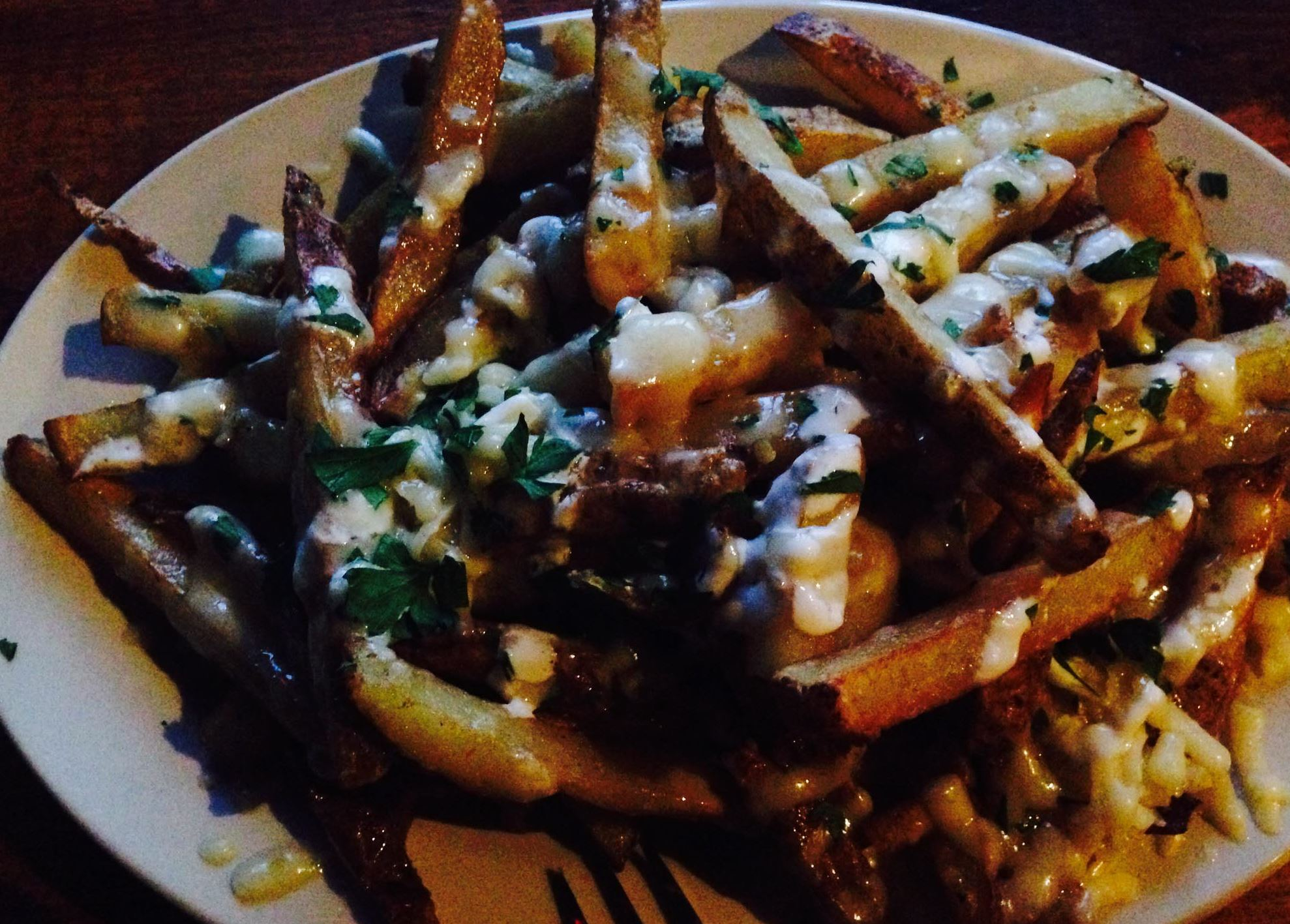 20140403MBMunch1 Polish fries are topped with creme fraiche and cheddar cheese, one of the specials on the menu for International Fries Night at Independent Brewing Company in Squirrel Hill.