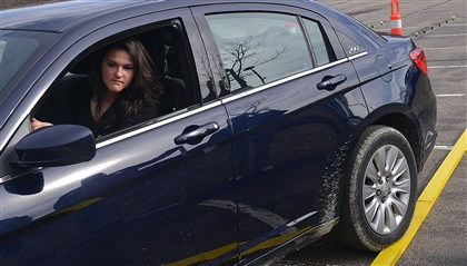 20140403lrdriving test09-1 Emily Garvin, 18, a senior at West Allegheny High School, looks into her mirror as she rolls her car onto the yellow line representing a curb during a parallel parking test. She was taking part in the fifth annual Teen Safe Driving Competition at Pittsburgh Technical Institute.