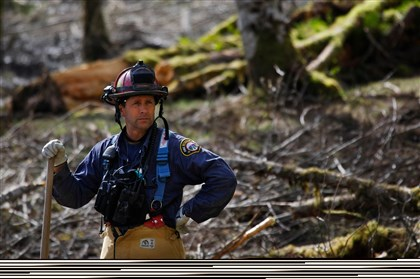 Washington Mudslide Capt. Jeff Zonrnes, of the Monroe Fire Department, looks on in the debris field, Wednesday as volunteers worked to clear more of the mudslide area in Oso, Wash. A deadly mudslide in March killed more than two dozen people.