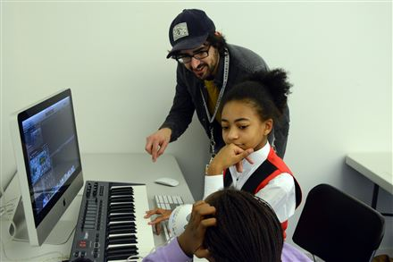"Andre Costello, a teen specialist at the Carnegie Library of Pittsburgh in East Liberty, teaches Chazzlyn Burke, center, 11, and Sydnie Jay, 12, to use musical software at ""The Labs"" program. Studies have found that for $1 of investment into libraries, $5.50 to $6 is returned to the community."