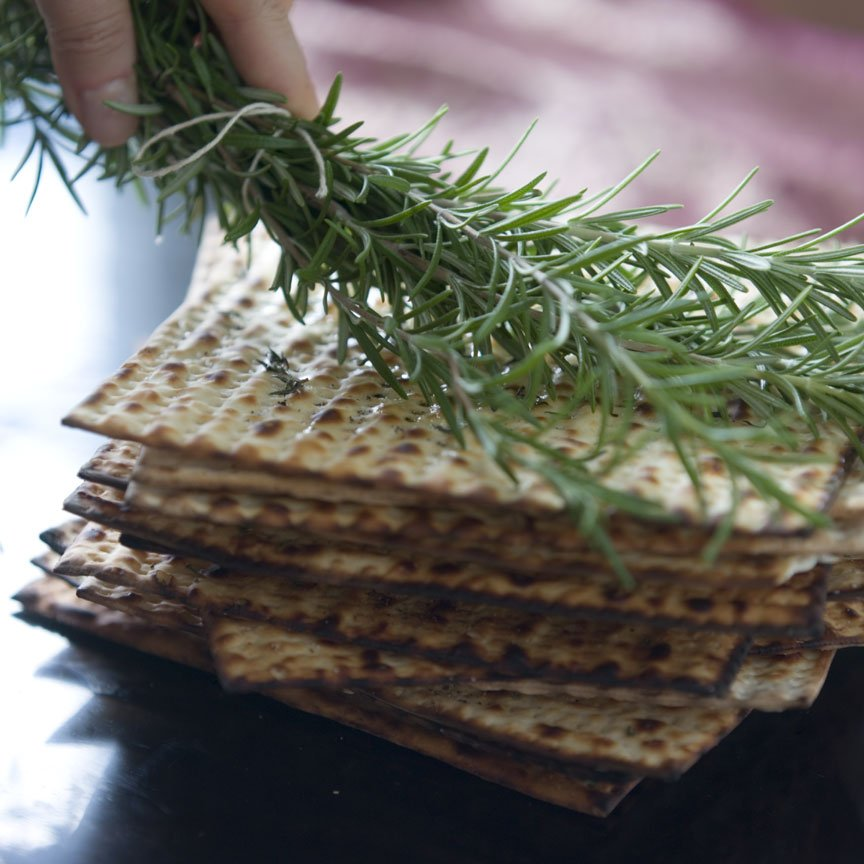 "20140403matzo-1 Matzo being brushed with rosemary from ""Jewish Holiday Cooking."""