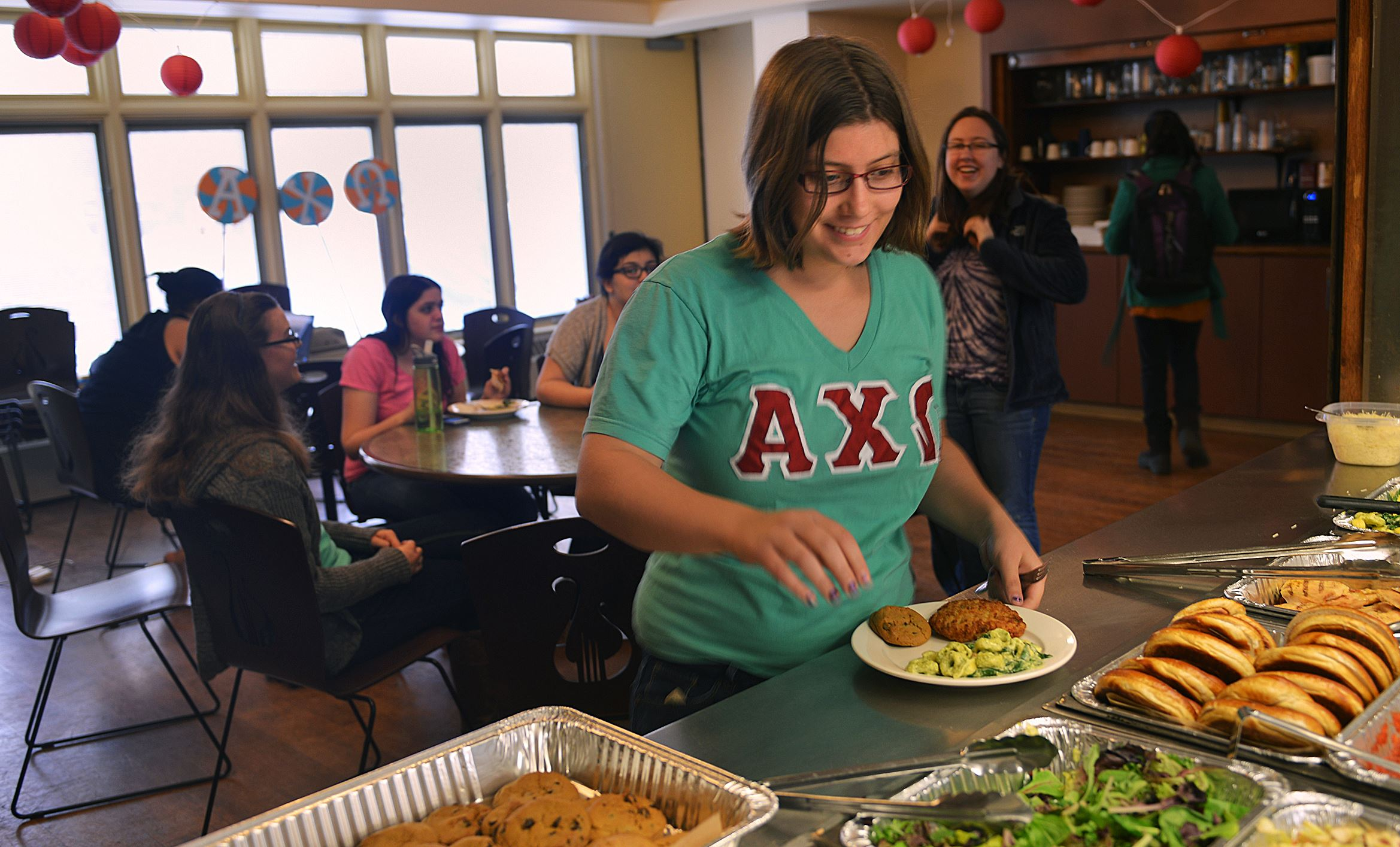 20140403lrsororityfood06-3  Annika Peterson, a 21-year-old junior, looks to add to her plate of oven-baked chicken breast, tortellini and a chocolate-chip cookie from the offerings for lunch at Alpha Chi Omega sorority created by Debbie Fajerski.