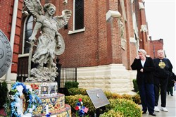 Gloria and Bob LeDonne of Bloomfield pause in front of the memorial honoring their relative, Pittsburgh police Officer Paul Sciullo II, as well as officers Eric Kelly and Stephen Mayhle, at St. Maria Goretti Parish in Bloomfield.