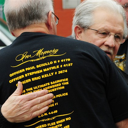 Paul Sciullo Paul Sciullo receives a hug before a memorial Friday honoring his son, Officer Paul Sciullo II, as well as Officers Eric G. Kelly and Stephen J. Mayhle. The memorial service marked five years since the three officers were killed.