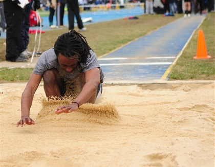 Daniel Commey, 17, of McDowell High School Daniel Commey, 17, of McDowell High School lands in the sand pit during the long jump competition at the Tri-State Track & Field Invitational at Titan Stadium on the campus of West Mifflin High School.