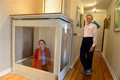 201441RARmaghome7-6 Mary Shaw rides the elevator while her husband Roy Weil holds the button in their Squirrel Hill home. The couple removed a closet and added the elevator that lies flat on the floor.