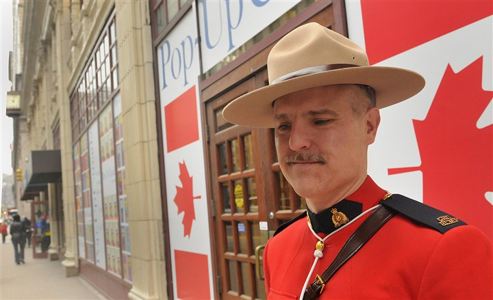 "20140407lrcanadalocal03 RCMP Constable Eric Hymander of Toronto poses outside the ""Pop-Up Canada"" storefront on Smithfield Street on Monday."