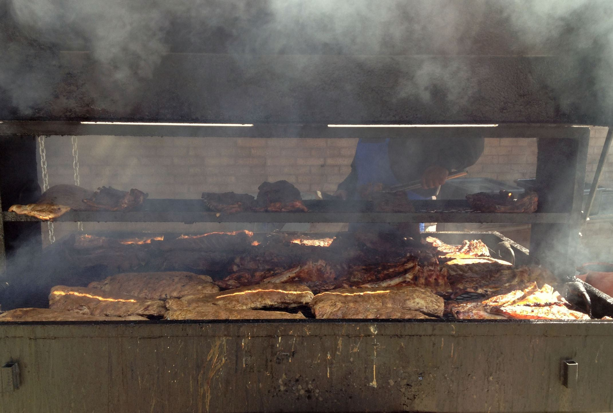20140410GiglerShowcaseBBQ3-2 Racks of ribs cook on one of the two massive grills at Showcase BBQ in Homewood.