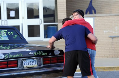 20140410JHLocalStab05-1 Sophomore Brad Hurt, right, is helped into car by his friend, senior Jack Bradley after Jack took Brett's photo in front of the school Thursday.