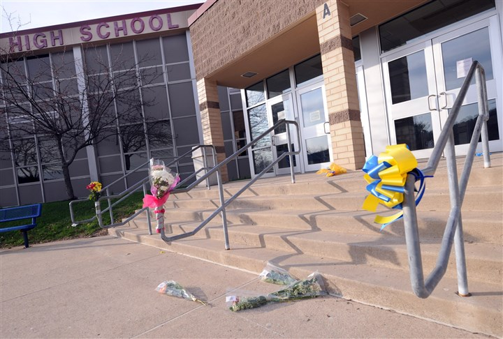 20140410JHLocalStab01 Flowers sit in front of the entrance to Franklin Regional High School, the site of Wednesday's knife attack.