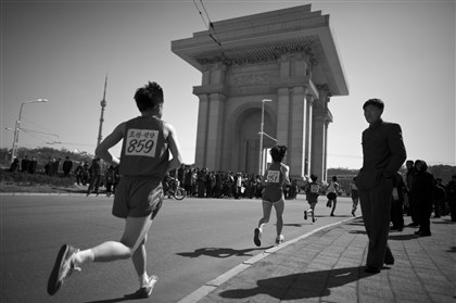 portfolio0412 Runners pass the Arch of Triumph in Pyongyang during last year's marathon.