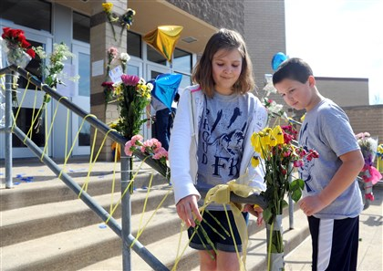 Corinne Mazure and Ryan Pagano Corinne Mazurek, left, 11, a student at Franklin Regional Middle School, and Ryan Pagano, 8, a student at Heritage Elementary school, tie ribbons around several hand rails and organize flowers on the steps at Franklin Regional High School on Saturday.