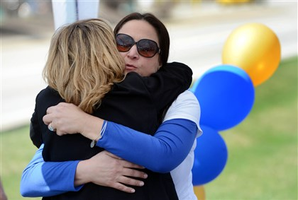 Michelle Milan McFall and Erin McClelland Michelle Milan McFall, in white, who is a mother with one daughter in the Franklin Regional School District, hugs Erin McClelland, the executive director of Arche Wellness, while volunteering at the banner signing in Murrysville.