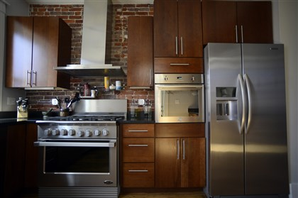 Lawrenceville row house, kitchen appliances Kitchen sports stainless steel appliances and cherry cabinetry.
