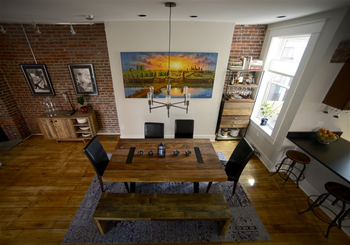 Lawrenceville row house, dining The dining area has exposed brick walls and 5-inch-wide pine planks.