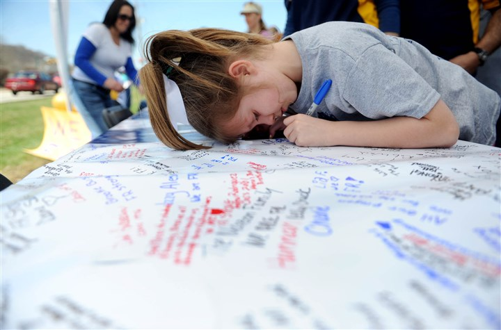 Jenna Joyce, 8, a third-grader at Sloan Elementary School Jenna Joyce, 8, a third-grader at Sloan Elementary School, signs a 28-foot-by-4-foot banner supporting the students of Franklin Regional High School in a parking lot off of Route 22 in Murrysville on Saturday. The banner will be hung near the school when classes resume.