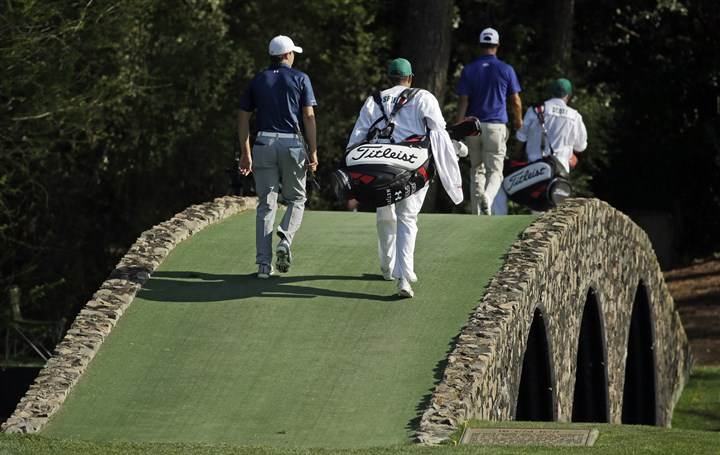Jordan Spieth, left, follows Adam Scott Jordan Spieth, left, follows Adam Scott, of Australia, across the Hogan Bridge with their caddies during the third round of the Masters golf tournament.