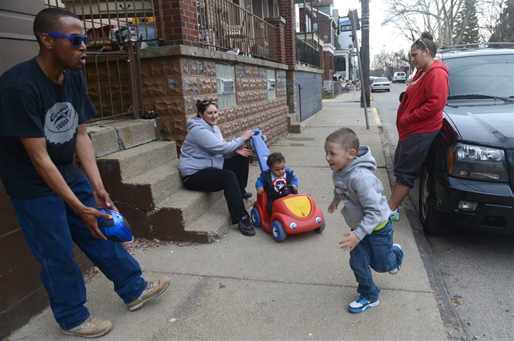 Robert Davis plays football with his son Aaden Leskowak Robert Davis, left, plays football with his son Aaden Leskowak, 3, as, from left, his mother Jenn Leskowak, brother Isaiah Davis, 9 months, and aunt Sammie Leskowak watch Thursday outside the Davis' home on Hatteras Street in Troy Hill.