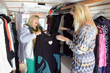 Ging's Style Truck fashion van Jackee Ging, right, helps customer Pam Palmer choose a dress in Ging's Style Truck fashion van last year.