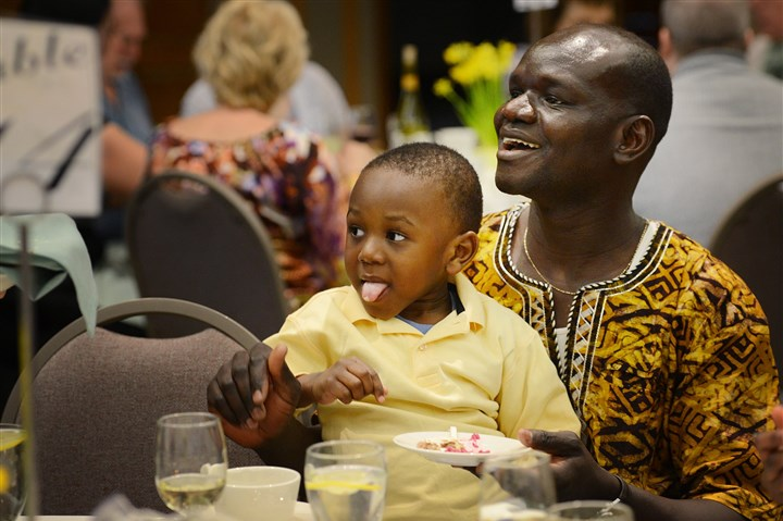 20140414jrSederLocal9-7 Benedict Killang, originally from South Sudan, holds his son Miracle, 2, on Monday while he tries his first bite of horseradish. They were attending his first Passover seder at Rodef Shalom Congregation in Oakland.