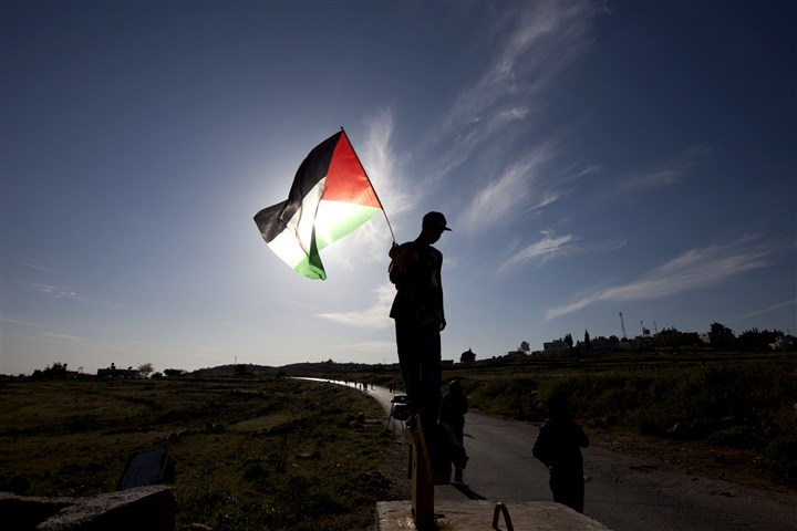 Mideast Israel Palestinians A protester holds a Palestinian flag at a checkpoint closed by Israeli soldiers after demonstrations against the expansion of the Jewish settlement Halamish in the West Bank.