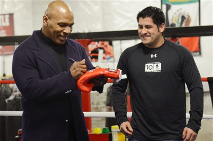 20140415jrTysonSports6 Mike Tyson signs a glove for Marine Carlos Jativa, 25, of Brookline.