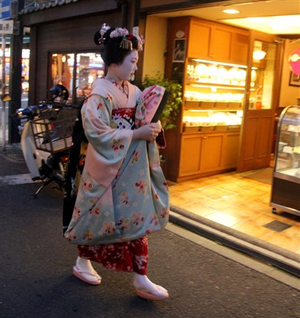 20140410psgeisha2mag0044-2 A real geisha in training, known as a maiko, on her way to an engagement in the Gion district of Kyoto, Japan.