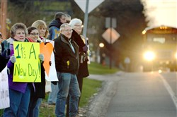 Supporters hold signs in front of the Newlonsburg Presbyterian Church as school buses return to Franklin Regional High School after the stabbing attacks last April.