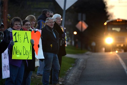 Signs of a New Day Supports hold signs early this morning in front of the Newlonsburg Presbyterian Church as students return to Franklin Regional High School.