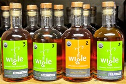 Bottles of Wigle wheat whiskey and rye whiskey sit on a shelf.