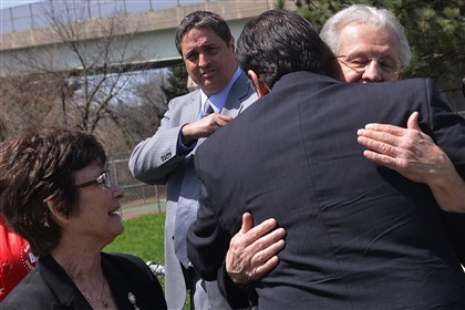 201404177lrhockeylocal02 Pittsburgh Mayor Bill Peduto gets a hug from Max Sciullo, right, father of slain Pittsburgh police officer Paul Sciullo as his wife Julia,, left, looks on at the press briefing announcing the building of a deck hockey rink in Bloomfield Park next to the ball field named after the Mr. Sciullo's son. In the rear is Pittsburgh Penguins CEO David Morehouse. Paul Sciullo, who lived in Bloomfield, was an avid hockey player.