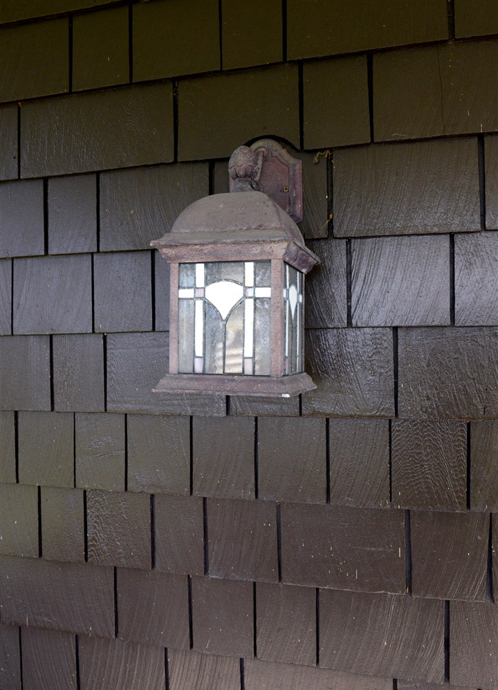 A lamp on an outside wall covered in shingles. A lamp on an outside wall covered in shingles.
