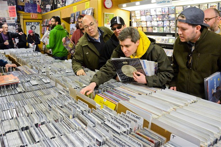 Sound Cat Record Ben Smith, 36, of Highland Park looks through rows of records while other customers look on at Sound Cat Records in Bloomfield on Saturday during Record Store Day.