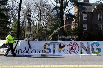 20140421bostonmarathon6-1 A police officer walks past a Boston Strong banner as Wellesley College students affix the banner to the barricades before the start of the 118th Boston Marathon Monda